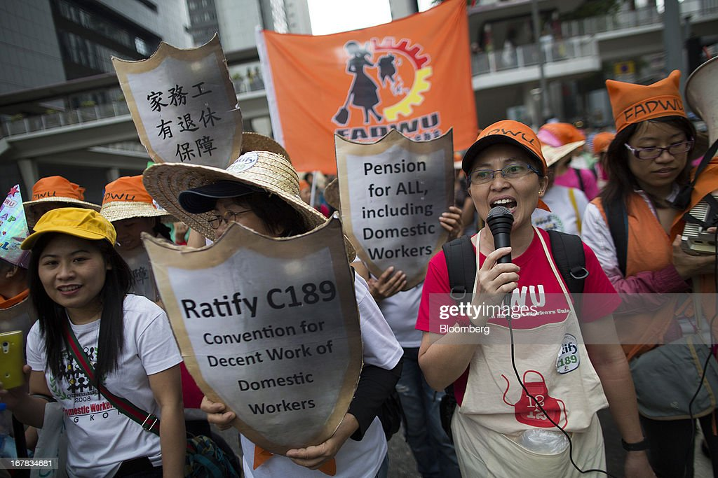 Domestic workers carry flags and chant slogans during a Labor Day march in Hong Kong, China, on Wednesday, May 1, 2013. Thousands of Hong Kong residents took to the streets today for Labor Day marches to petition for better labor conditions and in support of strike action by workers at docks operated by billionaire Li Ka-shing. Photographer: Jerome Favre/Bloomberg via Getty Images
