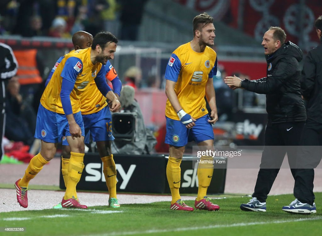 Domi Kumbela of Braunschweig celebrates his second goal with team mates and head coach Torsten Lieberknecht during the Bundesliga match between...