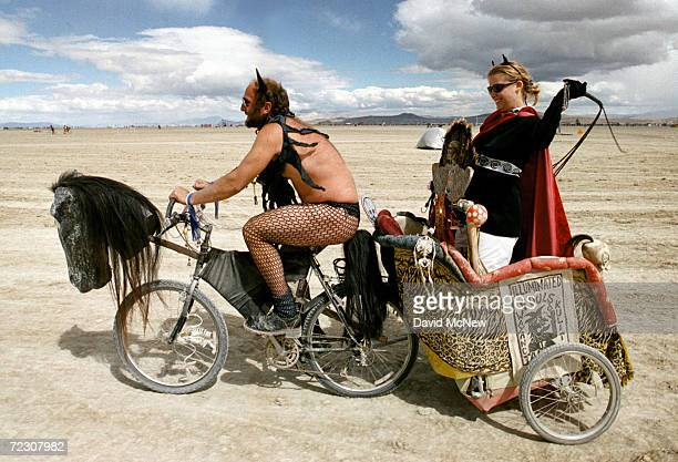 A dominating woman gets a chariot ride across the playa during the15th annual Burning Man festival September 2 2000 in the Black Rock Desert near...