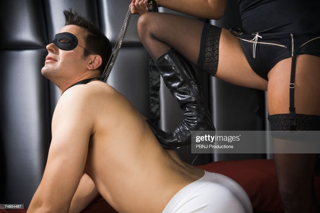 Dominatrix with foot on man's back : Stock Photo