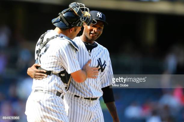 Domingo German and Austin Romine of the New York Yankees celebrate after defeating the Baltimore Orioles 143 at Yankee Stadium on June 11 2017 in the...