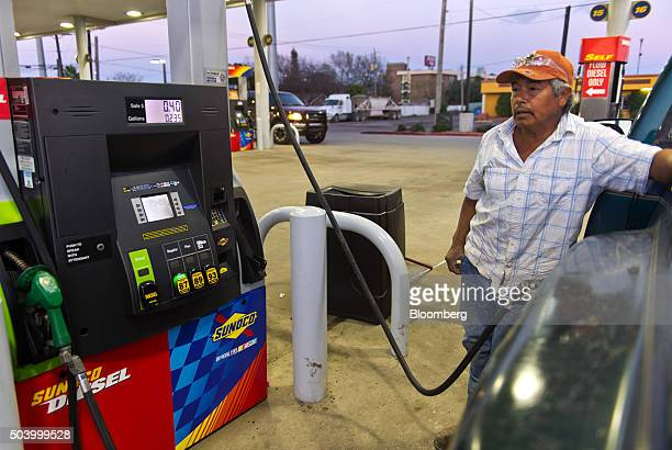 Domingo Lira pumps Sunoco gasoline into his truck at a Stripes convenience store in Corpus Christi Texas US on Thursday Jan 7 2016 Crude oil slid...