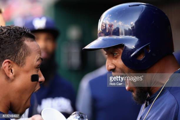 Domingo Santana of the Milwaukee Brewers celebrates with Orlando Arcia in the dugout after hitting a solo home run against the Washington Nationals...