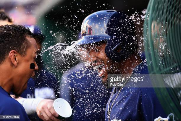 Domingo Santana of the Milwaukee Brewers is doused with water by Orlando Arcia in the dugout after hitting a solo home run against the Washington...