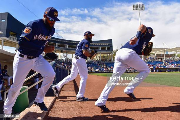 Domingo Santana Hernan Perez and Eric Thames of the Milwaukee Brewers take the field for the spring training game against the Texas Rangers at...