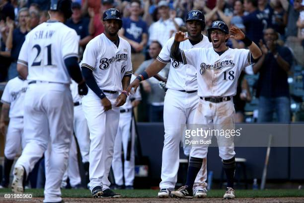 Domingo Santana Jesus Aguilar and Eric Sogard of the Milwaukee Brewers wait to congratulate Travis Shaw after Shaw hit a grand slam in the seventh...