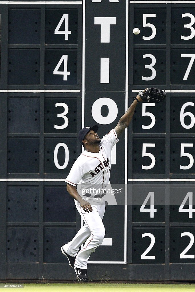 Domingo Santana #13 of the Houston Astros can't make a play on a fly ball off the wall in the fourth inning against the Seattle Mariners at Minute Maid Park on July 1, 2014 in Houston, Texas.