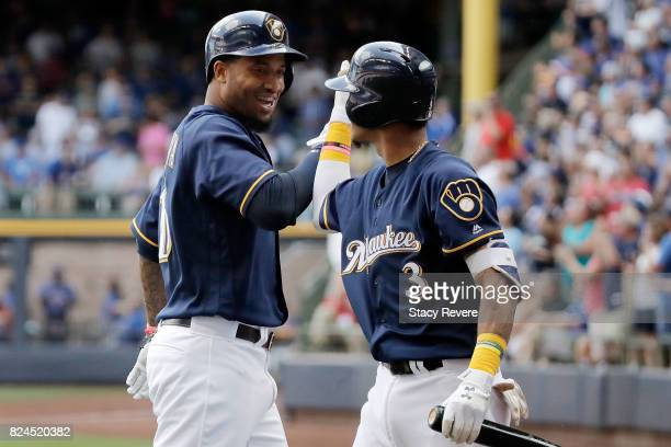 Domingo Santana of the Milwaukee Brewers celebrates a home run with Orlando Arcia during the sixth inning of a game against the Chicago Cubs at...
