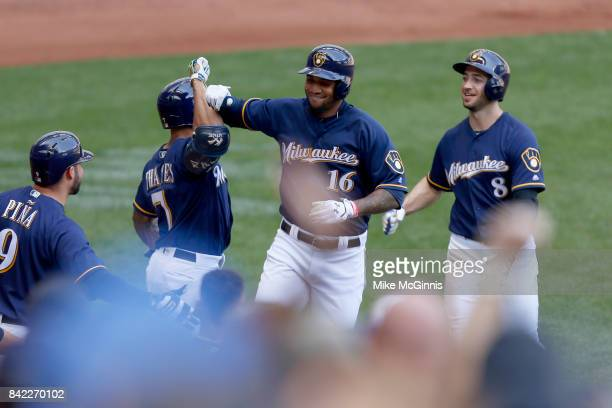 Domingo Santana of the Milwaukee Brewers celebrates with Eric Thames after hitting a two run homer in the fourth inning against the Washington...