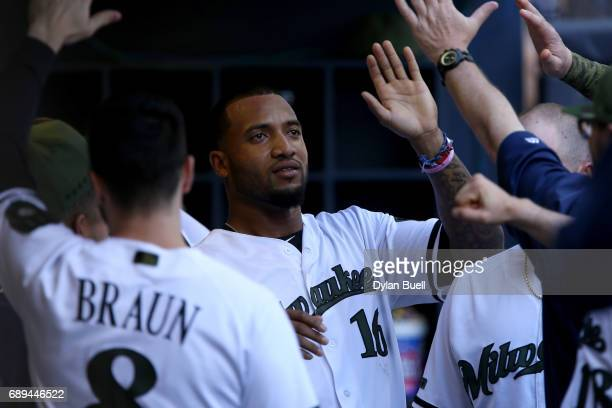 Domingo Santana of the Milwaukee Brewers celebrates with teammates after scoring a run in the first inning against the Arizona Diamondbacks at Miller...