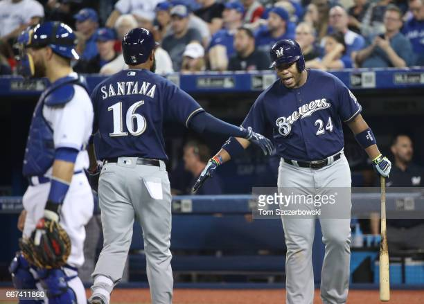 Domingo Santana of the Milwaukee Brewers is congratulated by Jesus Aguilar after hitting a solo home run in the fifth inning during MLB game action...