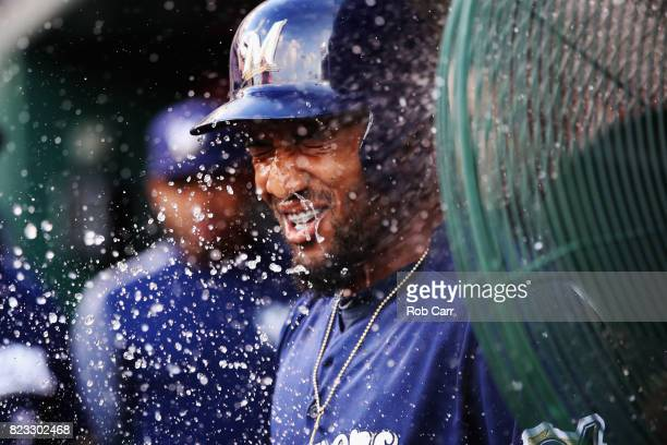 Domingo Santana of the Milwaukee Brewers is doused with water in the dugout after hitting a solo home run against the Washington Nationals in the...
