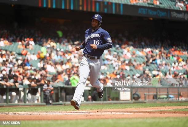 Domingo Santana of the Milwaukee Brewers runs home to score on a double hit by Travis Shaw in the first inning against the San Francisco Giants at...