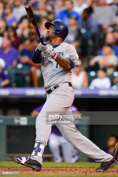 Domingo Santana of the Milwaukee Brewers watches the flight of a second inning solo homerun hit against the Colorado Rockies at Coors Field on August...