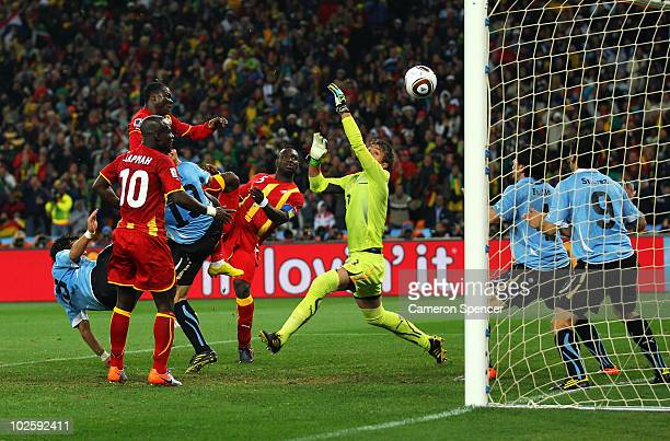 Dominic Adiyiah of Ghana heads on target as Luis Suarez of Uruguay handles the ball on the goal line for which he is sent off during the 2010 FIFA...