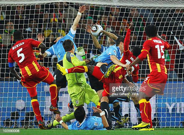 Dominic Adiyiah of Ghana heads the ball towards goal and Luis Suarez of Uruguay handles the ball off the line during the 2010 FIFA World Cup South...