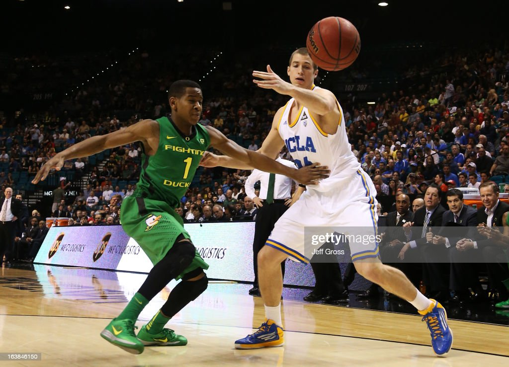 Dominic Artis #1 of the Oregon Ducks and Travis Wear #24 of the UCLA Bruins vie for a loose ball in the first half of the Pac-12 Championship game at MGM Grand Garden Arena on March 16, 2013 in Las Vegas, Nevada.