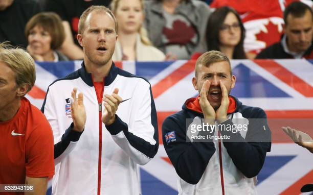 Dominic Inglot and Dan Evans of Great Britain cheer on their teammate Kyle Edmund during his singles match against Denis Shapovalov of Canada on day...