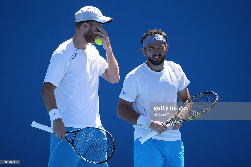 Dominic Inglot of Great Britain and Florin Mergea of Romania talk tactics in their first round doubles match against Matthew Ebden of Australia and...