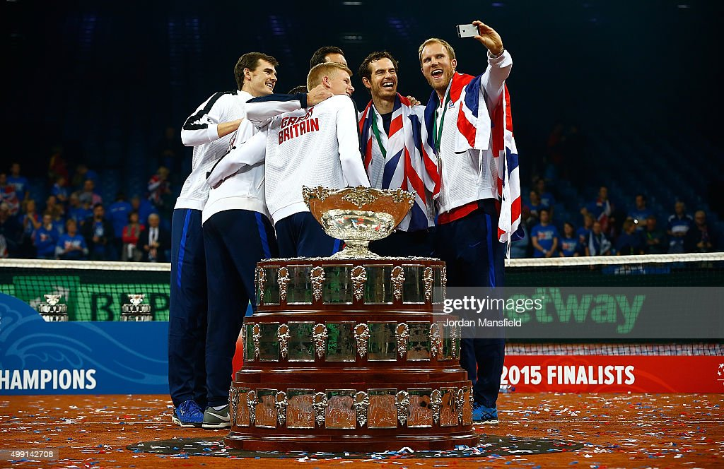 Dominic Inglot of Great Britain takes a selfie of his teammates with the trophy following their victory during day three of the Davis Cup Final match...
