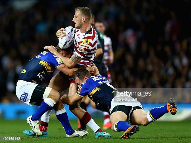 Dominic Manfredi of the Wigan Warriors is tackled by Danny McGuire of the Leeds Rhinos during the First Utility Super League Grand Final between...
