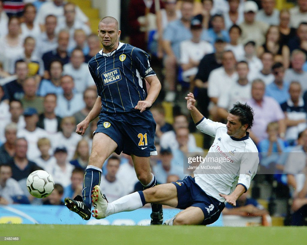 Dominic Matteo of Leeds United passes the ball as Helder Postiga of Tottenham Hotspur makes a challenge during the FA Barclaycard Premiership match held on August 23, 2003, at White Hart Lane, in London. Tottenham Hotspur won the match 2-1.