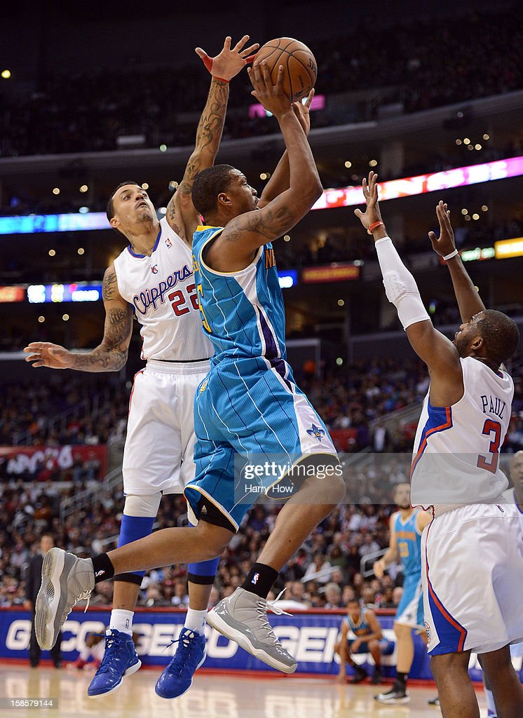 Dominic McGuire #5 of the New Orleans Hornets goes in for a layup between Matt Barnes #22 and Chris Paul #3 of the Los Angeles Clippers at Staples Center on December 19, 2012 in Los Angeles, California.