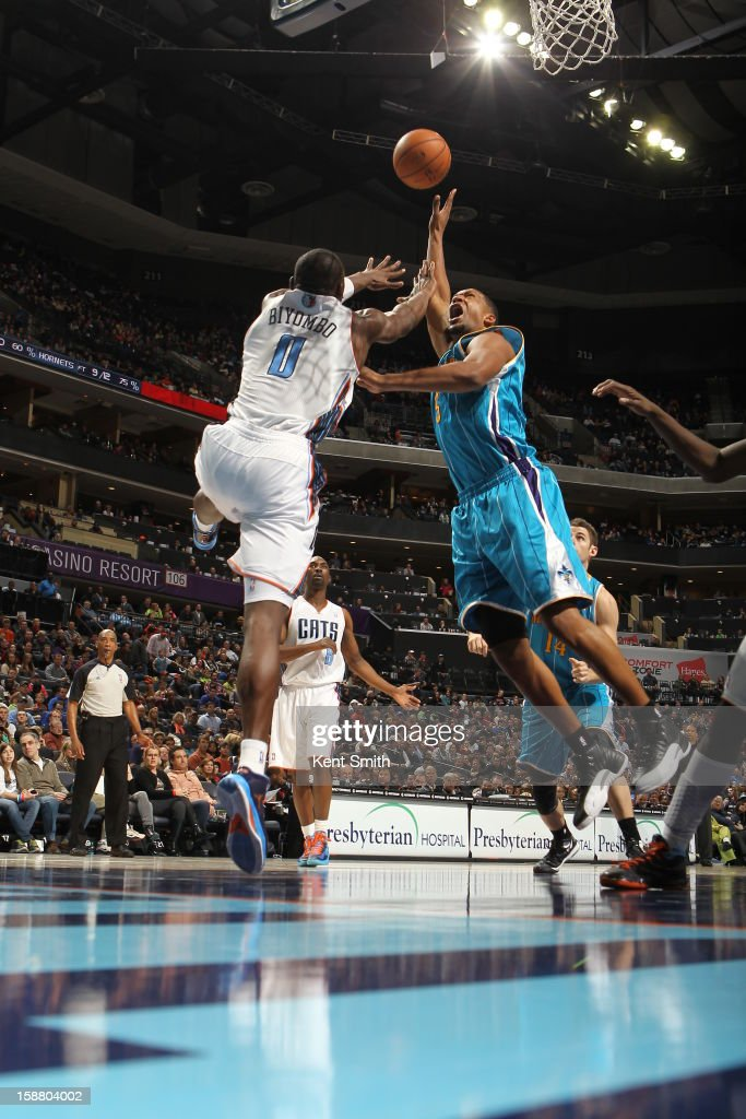 Dominic McGuire of the New Orleans Hornets shoots against Bismack Biyombo of the Charlotte Bobcats at the Time Warner Cable Arena on December 29 2012...
