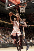 Dominic McGuire of the Toronto Raptors goes to the basket against Al Jefferson of the Utah Jazz during the game between the Toronto Raptors and the...