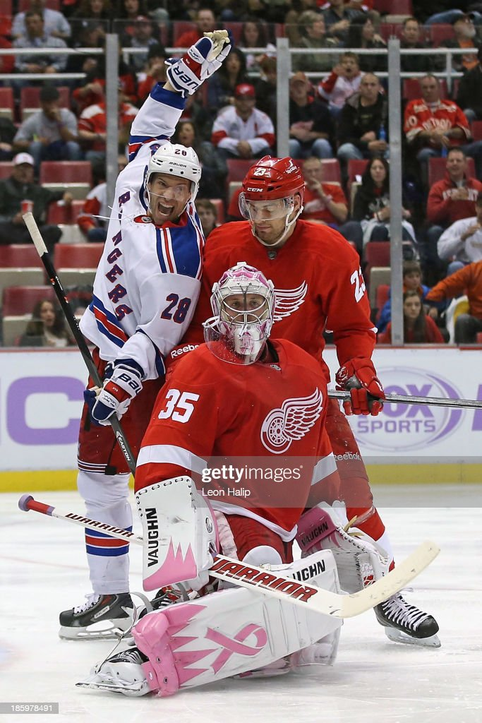 Dominic Moore of the New York Rangers celebrates the goal scored by teammate Mats Zuccarello as Brian Lashoff and goalie Jimmy Howard of the Detroit...