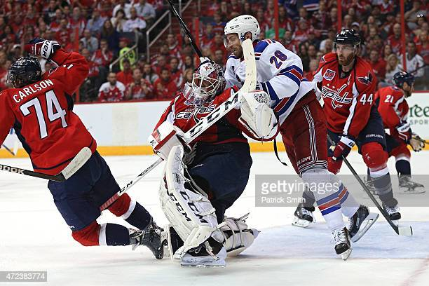 Dominic Moore of the New York Rangers collides with goalie Braden Holtby of the Washington Capitals during the second period in Game Four of the...
