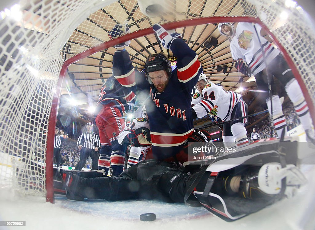 Dominic Moore #28 of the New York Rangers falls into the net after getting hit from behind by Kimmo Timonen #44 of the Chicago Blackhawks at Madison Square Garden on March 18, 2015 in New York City. The puck crossed the line but was ruled no goal because a whistle had blown.