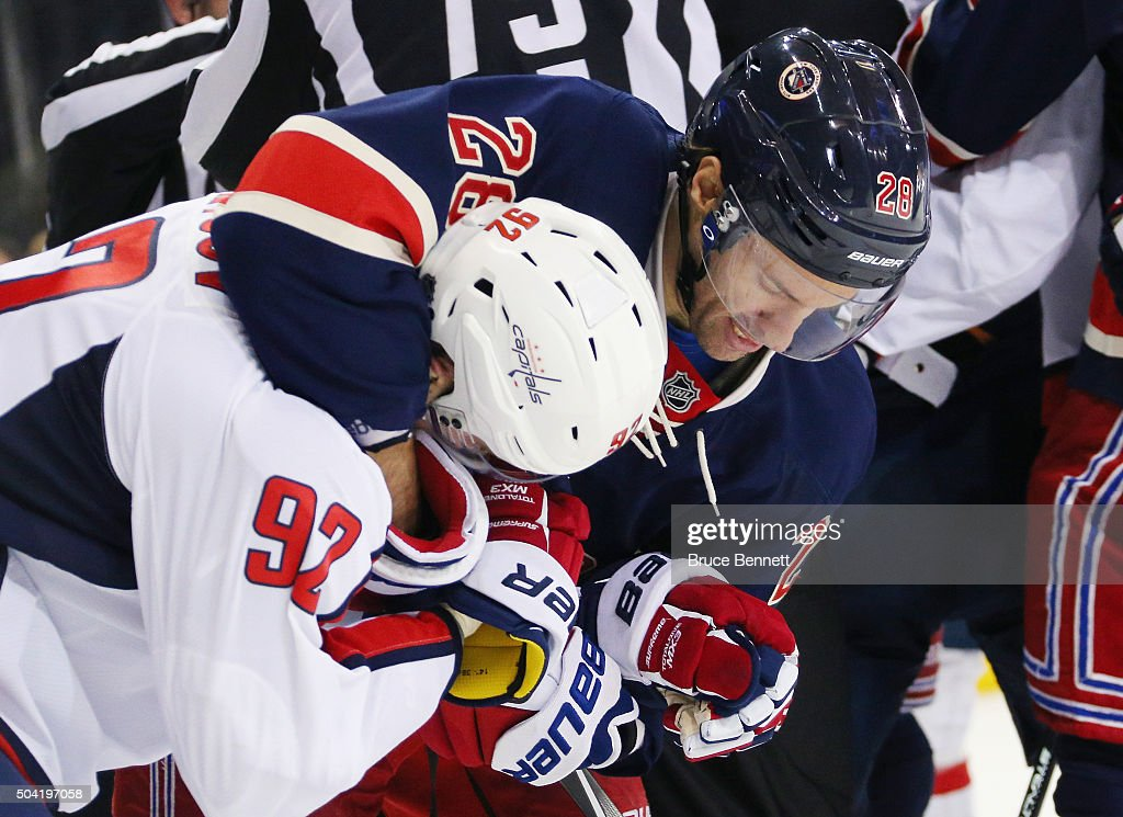 Dominic Moore #28 of the New York Rangers grabs a hold of Evgeny Kuznetsov #92 of the Washington Capitals at Madison Square Garden on January 9, 2016 in New York City. The Capitals defeated the Rangers 4-3 in overtime.
