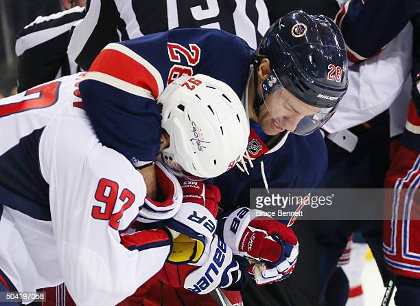 Dominic Moore of the New York Rangers grabs a hold of Evgeny Kuznetsov of the Washington Capitals at Madison Square Garden on January 9 2016 in New...