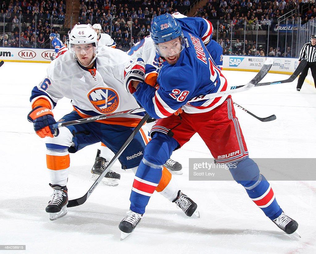 Dominic Moore #28 of the New York Rangers skates against Matt Donovan #46 of the New York Islanders at Madison Square Garden on January 21, 2014 in New York City.