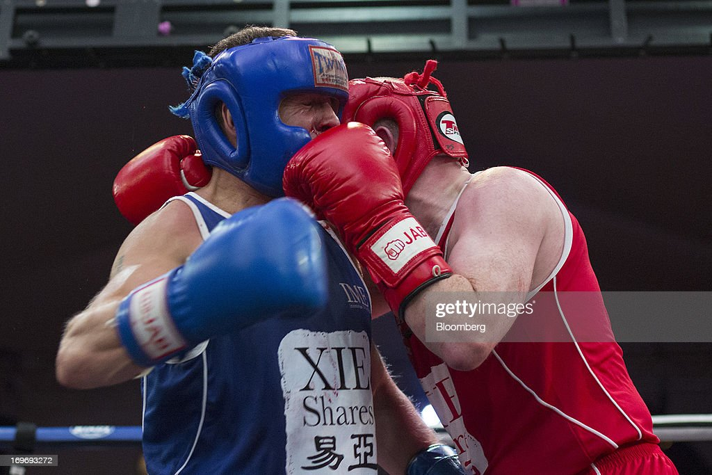 Dominic Smith, an area sales manager for HSBC Holdings PLC, in red, exchanges blows with Ashley Dale, chief executive officer of Mirae Assets Securities HK Ltd., in the second bout during the Hedge Fund Fight Nite 2013 charity fighting event in Hong Kong, China, on Thursday, May 30, 2013. The event raises money for Operation Breakthrough and Operation Smile charities. Photographer: Jerome Favre/Bloomberg via Getty Images