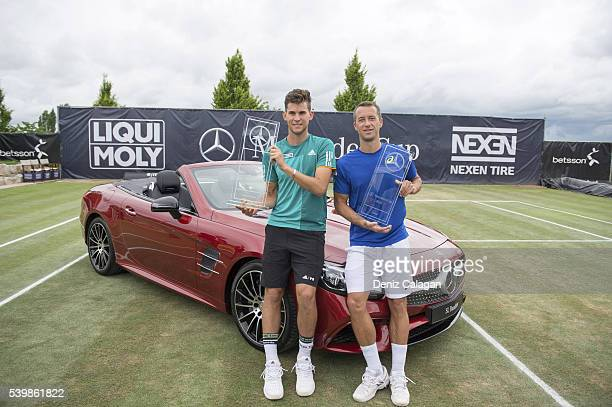 Dominic Thiem of Austria and Philipp Kohlschreiber of Germany pose with their trophies in front of the prize car after the final match on day 10 of...