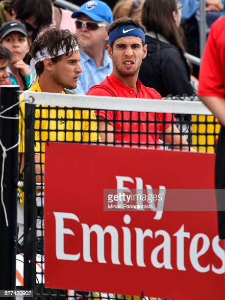 Dominic Thiem of Austria and teammate Karen Khachanov of Russia look on while taking a break against Nicholas Monroe and Jack Sock of the United...