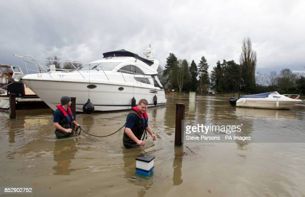 Dominic Webb and Stuart Williams from Lindon Lewis Marine check boats moored to flooded moorings next to the River Thames in Shepperton Surrey