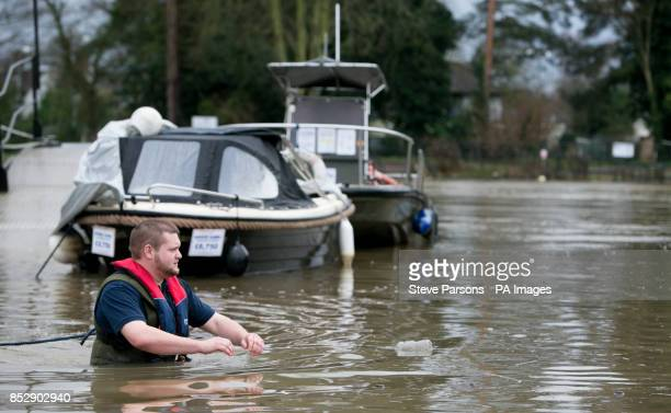 Dominic Webb from Lindon Lewis Marine check boats moored to flooded moorings next to the River Thames in Shepperton Surrey