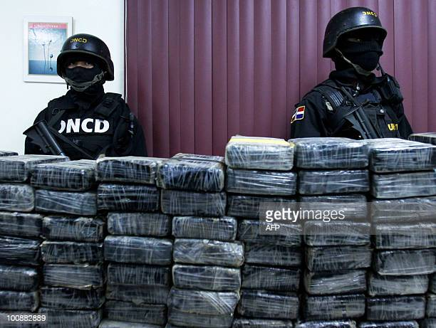 Dominican drug squad members stand guard behind packages containing cocaine part of a 1636 kg seizure on May 25 2010 in Santo Domingo Eight people...