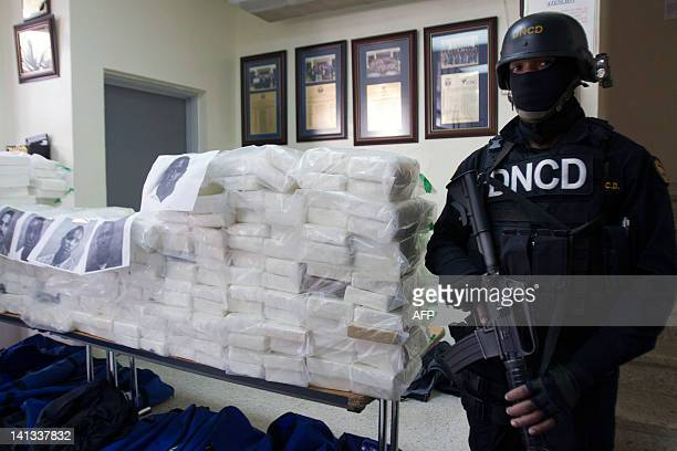 Dominican drug squad policemen stand guard next to packs containing 8074 kilos of cocaine confiscated by the Dominican National Direction of Drugs...