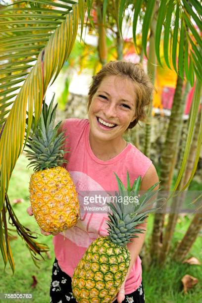 Dominican Republic, portrait of laughing young woman with pineapples