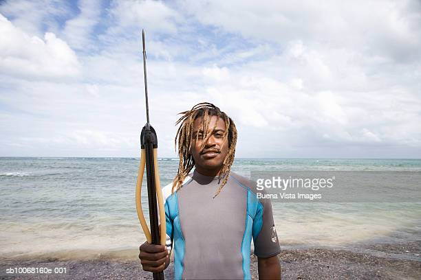Dominican Republic, Samana Peninsula, Las Terrenas, fisherman standing on beach holding spear, portrait