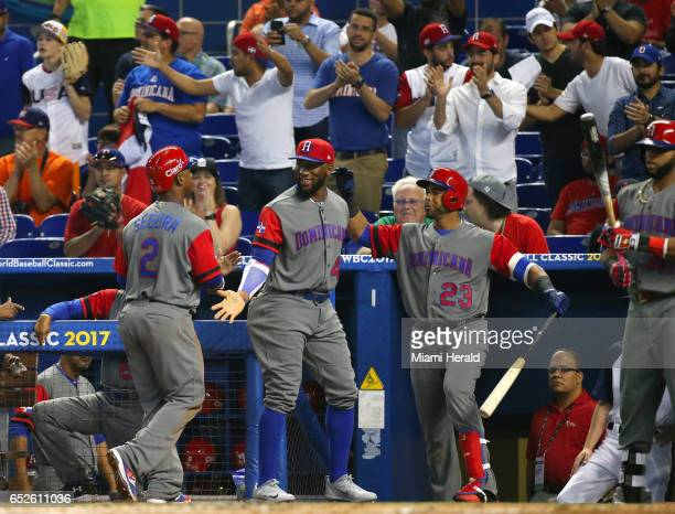 Dominican Republic shortstop Jean Segura is congratulated by teammates after scoring on a sacrifice fly by left fielder Jose Bautista during the...