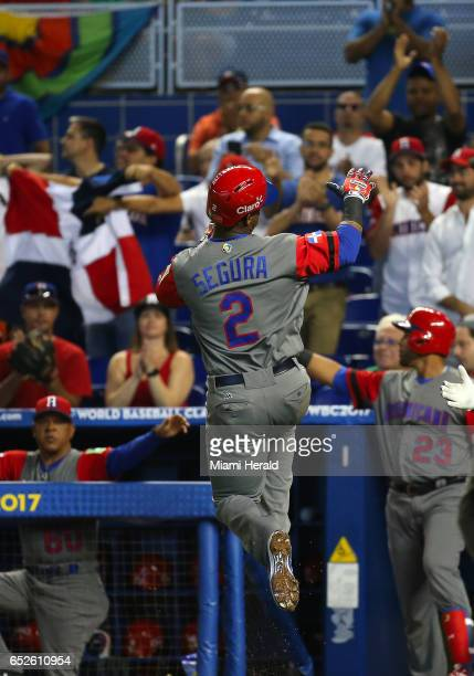 Dominican Republic shortstop Jean Segura jumps after scoring on a sacrifice fly by left fielder Jose Bautista during the first inning of a World...