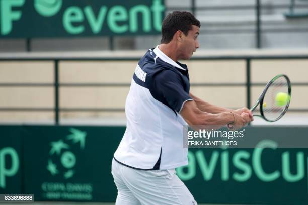 Dominican tennis player Roberto Cid returns the ball to Chilean Christian Garin during their Davis Cup World Group first round singles tennis match...