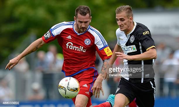 Dominick Drexler of Aalen is challenged by Dominik Schmidt of Kiel during the third league match between VfR Aalen and Holstein Kiel at ScholzArena...