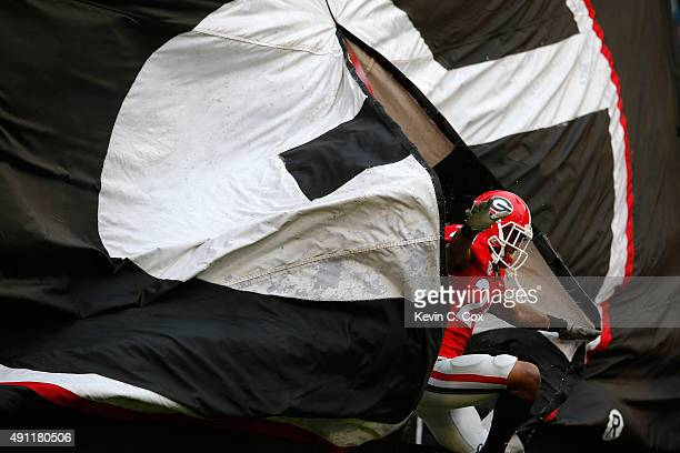 Dominick Sanders of the Georgia Bulldogs breaks through the banner prior to the game against the Alabama Crimson Tide at Sanford Stadium on October 3...