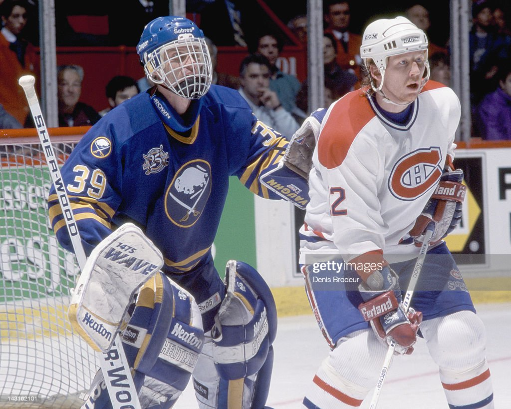 Dominik Hasek of the Buffalo Sabres is screened by Mike Keane of the Montreal Canadiens Circa 1995 at the Montreal Forum in Montreal Quebec Canada